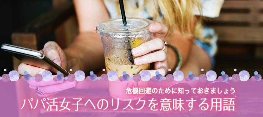アイスカフェラテを片手にスマートフォンを観る女性